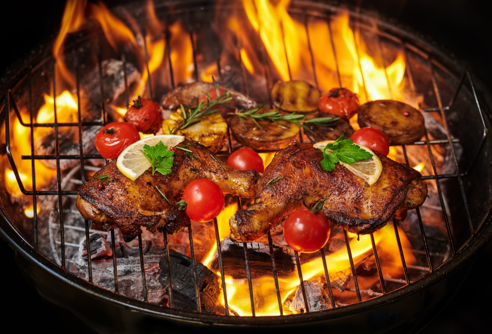grilled-chicken-legs-flaming-grill-with-grilled-vegetables-with-tomatoes-potatoes-pepper-seeds-salt